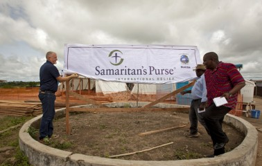 Kendell Kauffeldt, Samaritan's Purse Country Director, Liberia, and Dr Moses Massaquoi of the Liberia Ministry of Health and Social Welfare together unveil the new banner for the Foya Case Management Centre